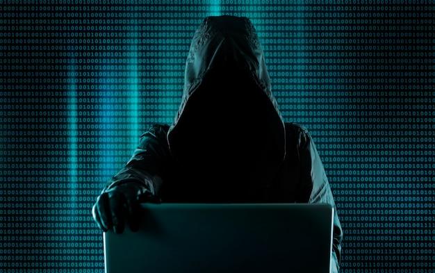 Hacksysteem, cybercrimineel achter een laptop, digitale binaire code op de achtergrond. hacker breekt in op het systeem