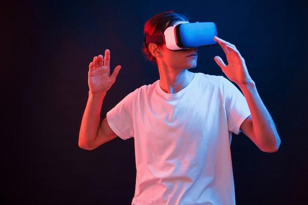 Had dat niet verwacht. jonge man met behulp van virtual reality-bril in de donkere kamer met neonverlichting