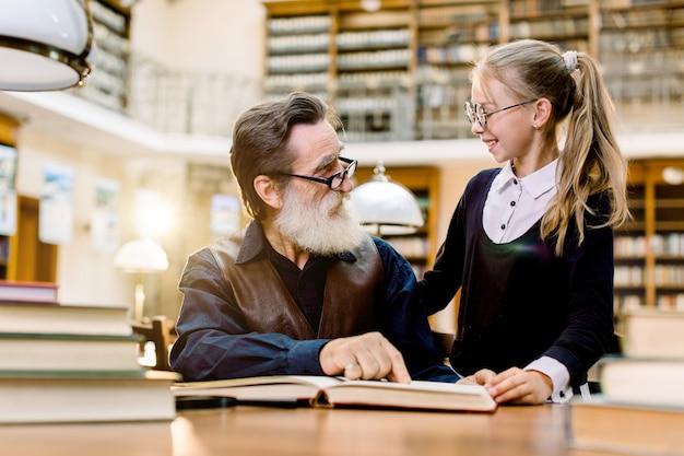 Hadsome bebaarde senior man grootvader en kleine schattige kleindochter samen boeken lezen, glimlachen en elkaar kijken, zittend in oude vintage bibliotheek