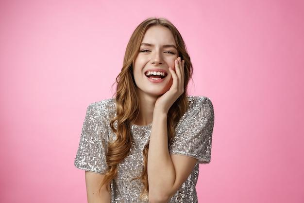 Haha zo grappig. flirterige, kokette, aantrekkelijke blanke vrouw lachend aanraken van gezicht vrouwelijk verleidingsgebaar giechelen interesse tonen geamuseerd praten, plezier hebben, genieten van cool feest, roze achtergrond