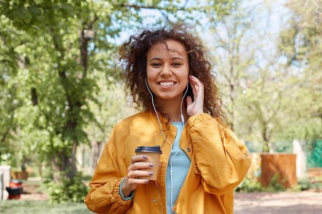 Hahhy schattige krullende donkere dame breed glimlachend, gekleed in een geel jasje, wandelen in het park, een kopje koffie vasthoudend, luisterende naar muziek en genietend van het weer.