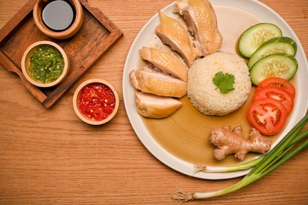 Hainanese kiprijst met sauzen komkommer en tomaat schuif gember en lente-ui op houten tafel
