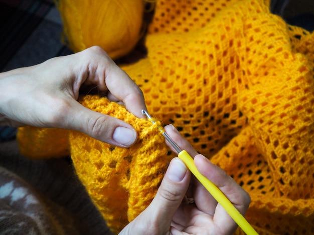 Haken vrouw haak geel garen. close-up van de handen.