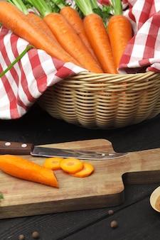 Hakkende gezonde wortelen op plak op hakbord in de keuken