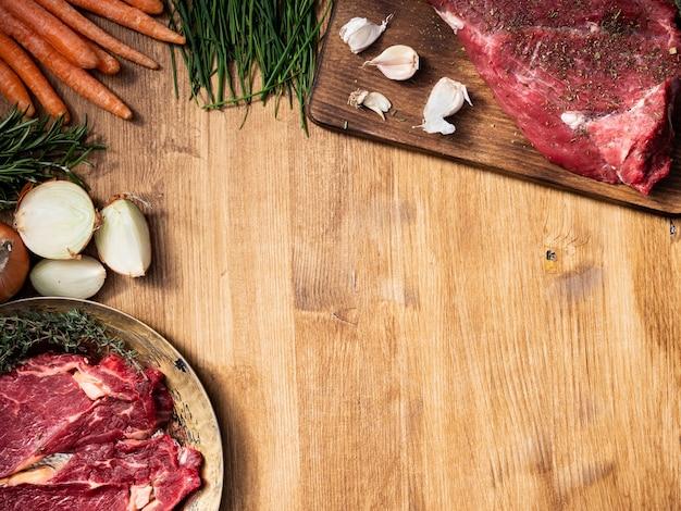 Hakkende snijplank met een groot stuk rood vlees erop kopieer de ruimte. witte uien. knoflook. natuurlijk eiwit.