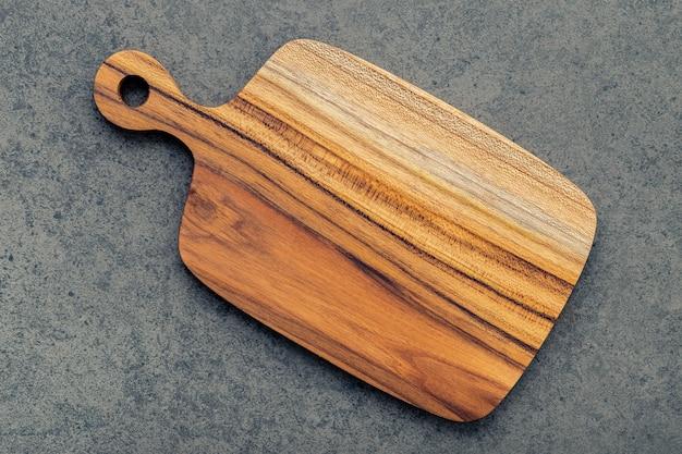 Hakkende teak houten scherpe raad op donkere steenachtergrond.