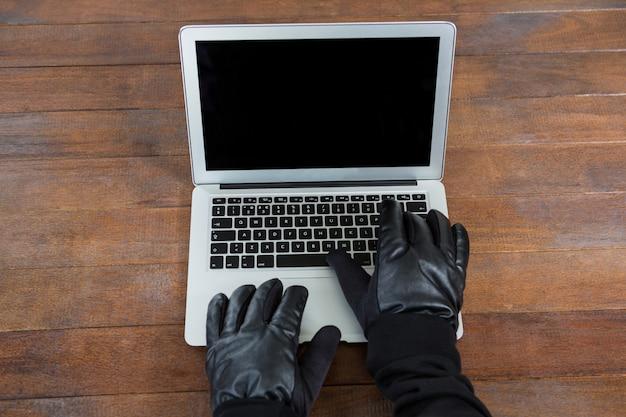 Hakker die laptop met behulp van bij bureau