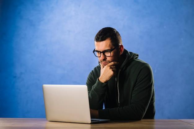Hakker met glazen die laptop bekijken