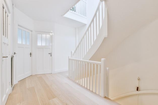 Hal met houten vloer en witte muren met glazen deuren en trap op en neer