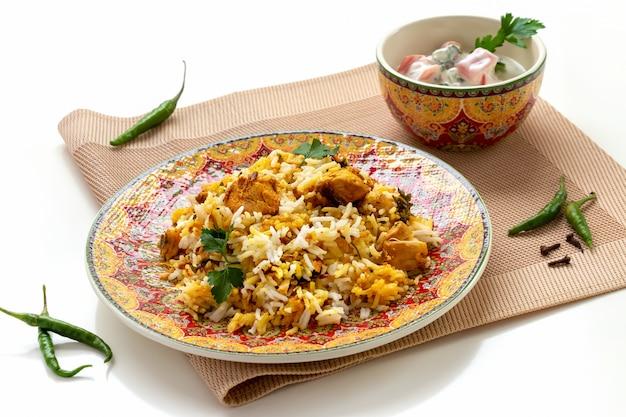 Halal indiase kip biryani geserveerd met raita van yoghurttomaat