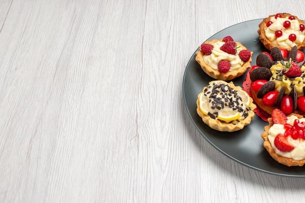 Half bovenaanzicht chocoladetaart afgerond met bessentaartjes in de grijze plaat op de witte houten tafel met kopie ruimte