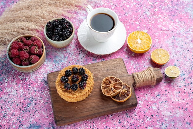 Half-bovenaanzicht frambozen en bramen in kleine potten met kopje thee cake op lichtroze achtergrond.