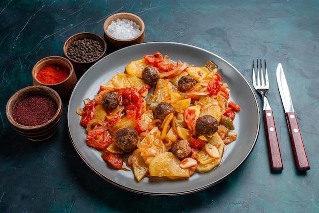 Half-bovenaanzicht gebakken aardappelen met gehaktballen en groenten samen met kruiden op donkerblauw bureau.