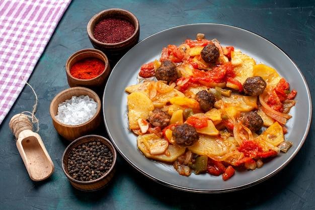 Half-bovenaanzicht gekookte gesneden aardappelen met gehaktballen samen met kruiden op donkerblauw bureau.
