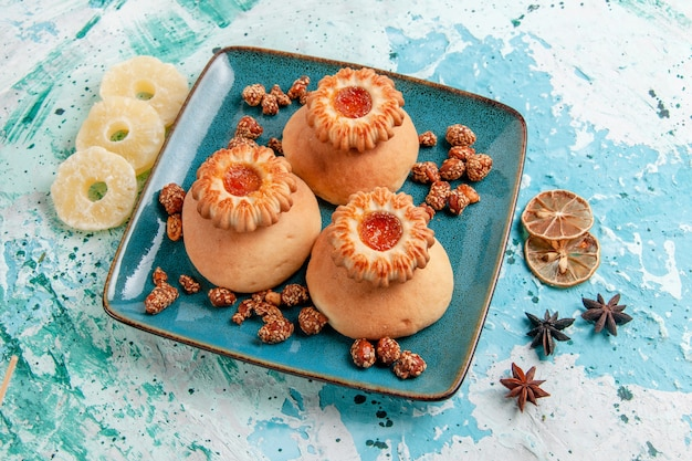 Half-bovenaanzicht heerlijke koekjes met gedroogde ananasringen op lichtblauwe oppervlakte koekjeskoekje zoete suikerkleur