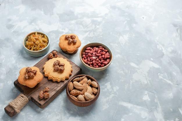 Half-bovenaanzicht kleine cakes met pistachenoten en noten op licht-witte achtergrond.