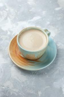 Half bovenaanzicht kopje koffie met melk in beker op het witte bureau drinkt koffiemelk bureau kleur