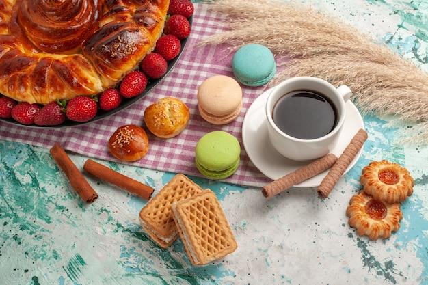 Half-bovenaanzicht lekkere zoete taart met rode aardbeien franse macarons en thee op lichtblauw bureau