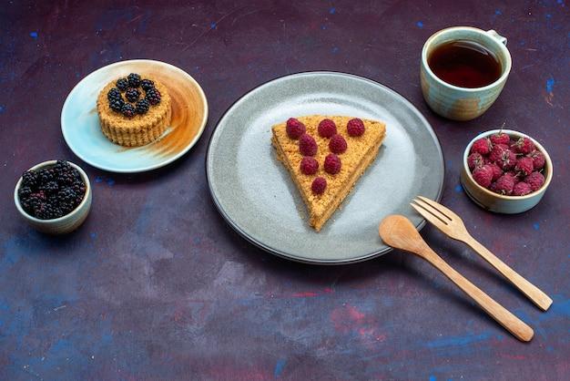 Half-bovenaanzicht van cakeplak heerlijk met frambozen en thee op donkere ondergrond