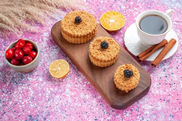 Half-bovenaanzicht van kleine heerlijke taarten ronde gevormd met kaneel en thee op lichtroze oppervlak