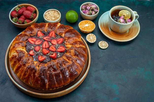 Half-bovenaanzicht van lekkere aardbeientaart gebakken heerlijke cake met kopje thee