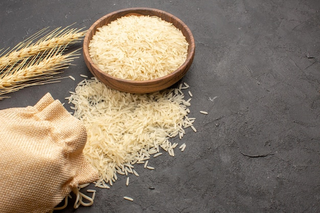 Half-bovenaanzicht van rauwe rijst in bruine plaat op donkergrijs oppervlak