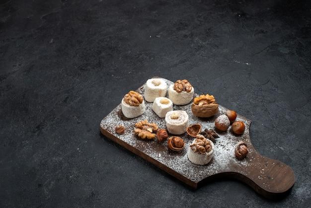 Half bovenaanzicht verschillende koekjes met cakes en walnoten op het donkergrijze oppervlak cake biscuit suiker bak zoete koekjes