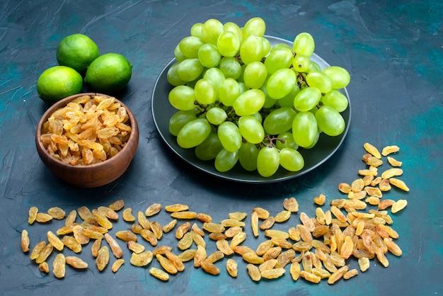 Half-bovenaanzicht verse groene druiven met citroenen op donkerblauw bureau.
