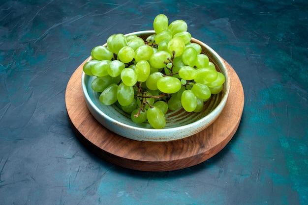 Half bovenaanzicht verse groene druiven, zacht sappig fruit in plaat op het donkerblauwe bureau.