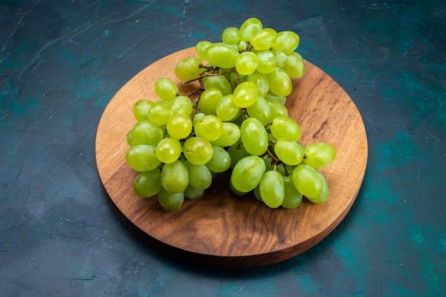Half bovenaanzicht verse groene druiven, zacht sappig fruit op donkerblauw bureau.
