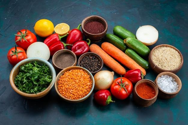 Half-bovenaanzicht verse groenten met greens en kruiden op donkerblauw bureau.