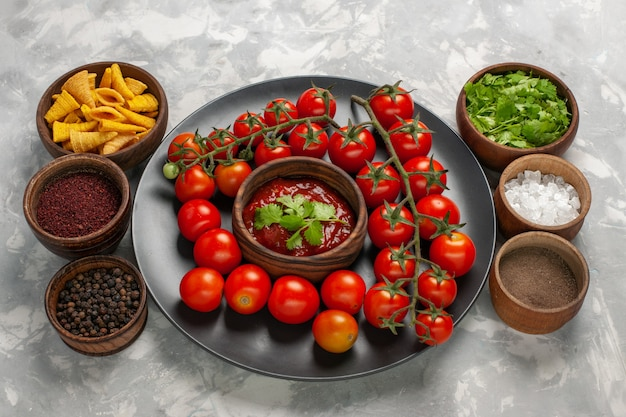 Half-bovenaanzicht verse kerstomaatjes in plaat met tomatensaus en verschillende kruiden op witte ondergrond