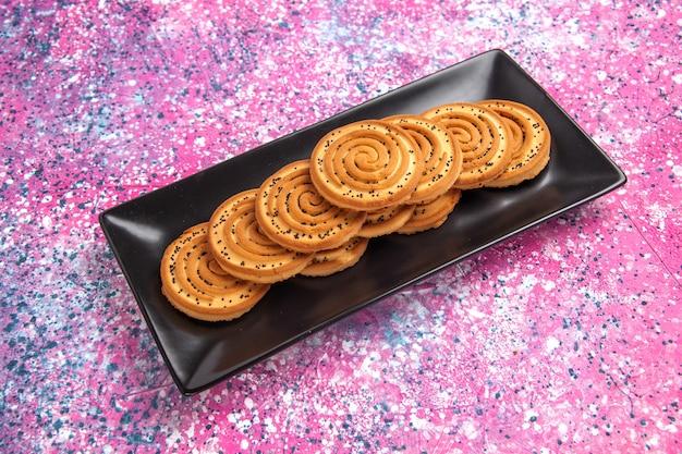 Half-bovenaanzicht zoete koekjes heerlijke kleine koekjes in zwarte vorm op lichtroze bureau.