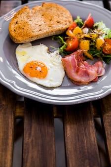Half gebakken ei; geroosterd brood; salade; spek op grijze keramische plaat op houten tafel