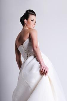 Half gedraaide bruid gekleed in witte trouwjurk