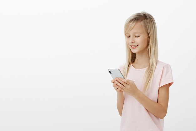 Half-gedraaide profielschot van slimme creatieve vrouwelijke kind met blond haar in roze t-shirt, smartphone vasthouden en glimlachen naar het scherm, grappig spel spelen op apparaat, genieten van tijd doorbrengen over grijze muur