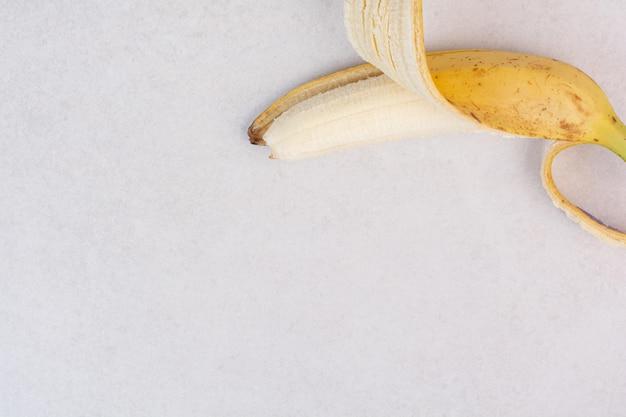 Half gepelde enkele banaan op wit oppervlak.