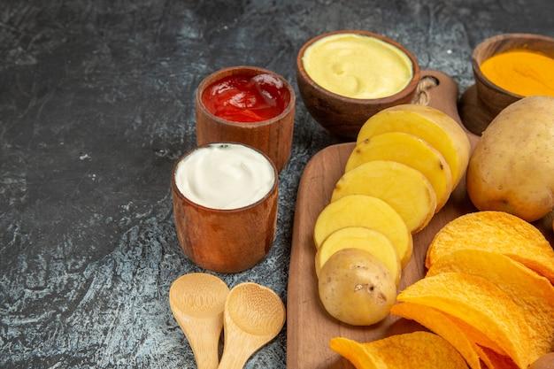 Half geschoten weergave van knapperige chips en ongekookte aardappelen op houten snijplank en verschillende kruiden op grijze tafel