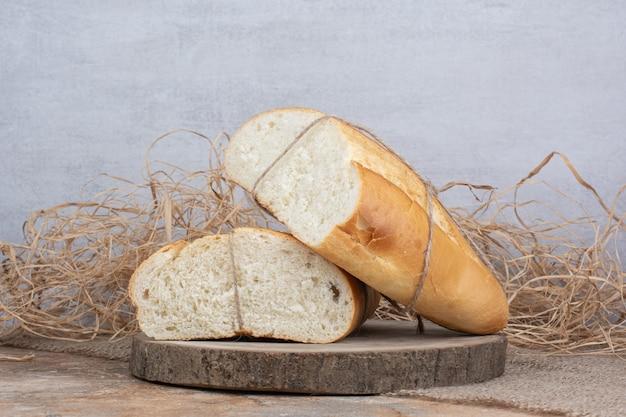 Half gesneden brood vastgebonden met touw op houten stuk