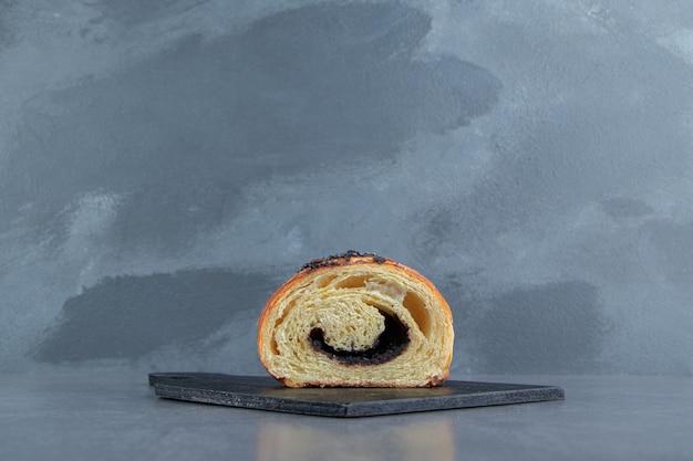Half gesneden croissant met chocolade op zwart bord.