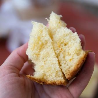 Half gesneden eigengemaakt zoet pasen-brood in de handen van de vrouw van een bakker. plakje orthodoxe zoet brood van pasen. mooie kantkruimels rollen. sluit omhoog, selectieve nadruk, exemplaarruimte.