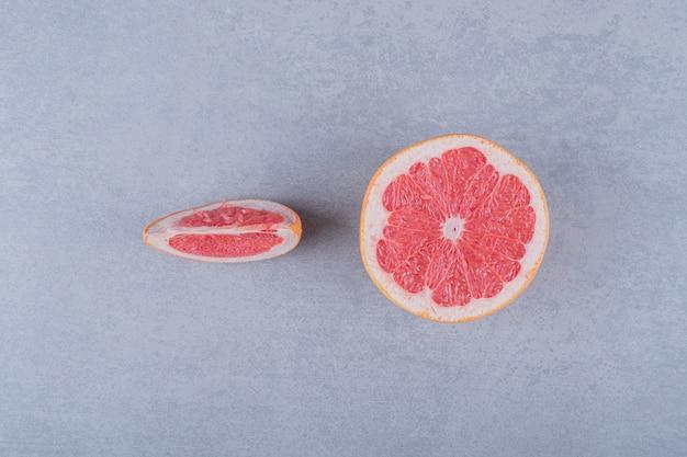 Half gesneden en plakje grapefruit op een grijze ondergrond