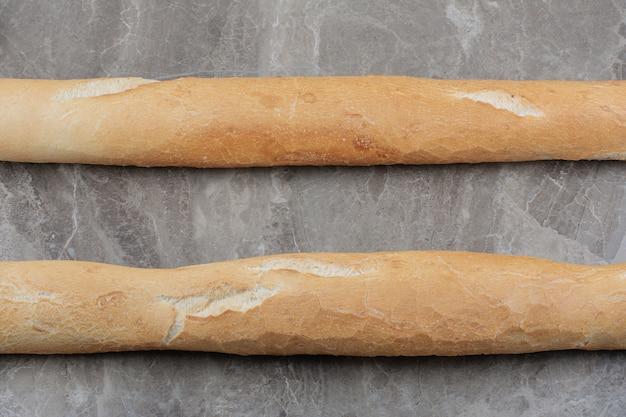 Half gesneden frans stokbrood op marmeren ondergrond