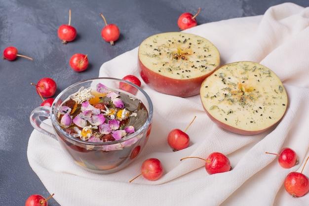Half gesneden fruit, kersen en glas sap met schijfje citroen en bloemen op blauw met tafellaken
