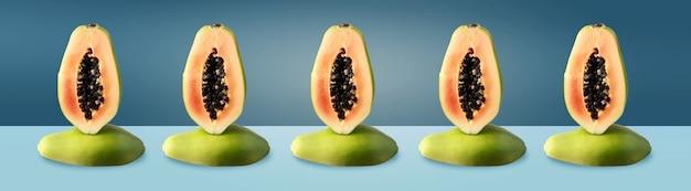 Half gesneden groene papaja op blauwe achtergrond, evenwichtsconcept, panoramisch beeld.