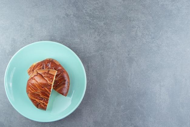 Half gesneden huisgemaakt gebak op blauw bord.