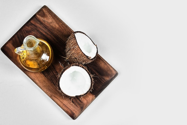 Half gesneden kokosnoot en fles olie op een houten bord.