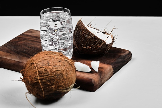Half gesneden kokosnoot op een houten bord en glas water met ijs.