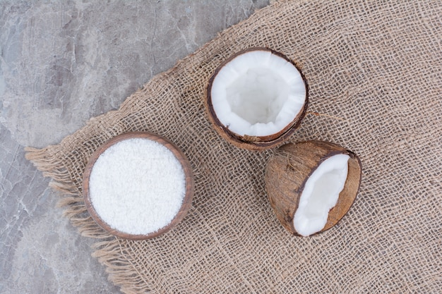 Half gesneden kokosnoten en kom met suiker op stenen oppervlak.