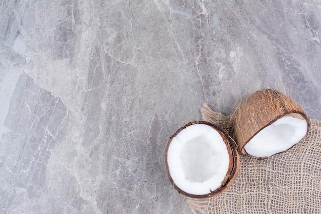 Half gesneden kokosnoten met jute op stenen oppervlak.